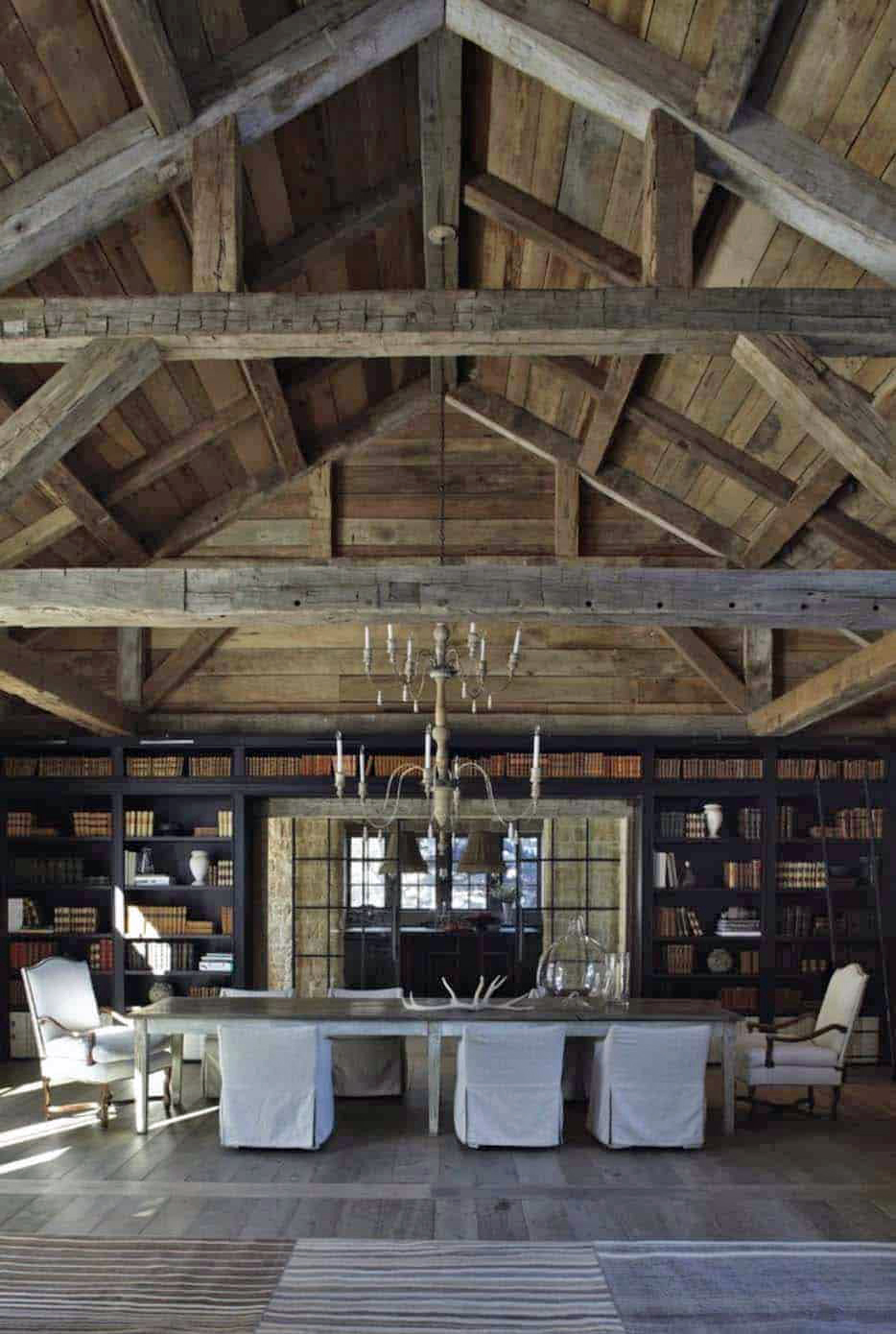 A dining table in a large scale barn style house.