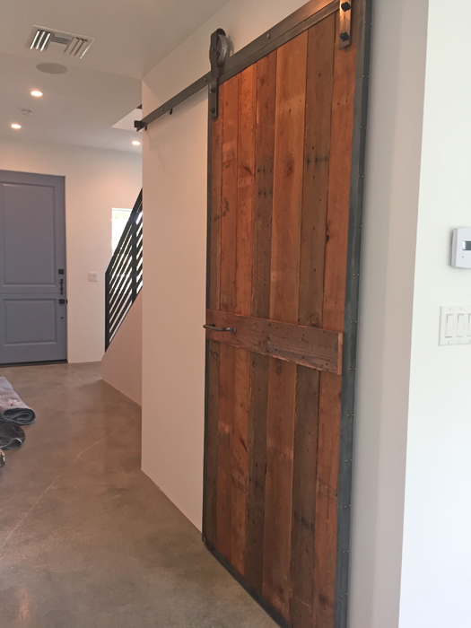 Downstairs sliding barn door at the Palm Modern Farmhouse. This door was fabricated with steel and wood from the original house.